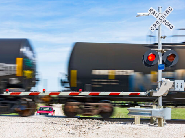 Blurred tanker cars going through a level crossing with safety gate down