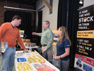 Two men and a woman talking at a community fair