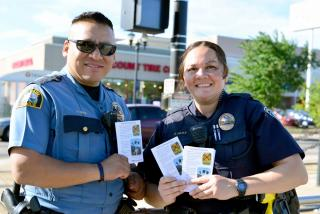 law enforcement officers distribute brochures with OLI safety tips for drivers