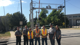 group of people standing near a railroad crossing
