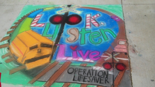 an image of a chalk drawing depicting rail safety messages