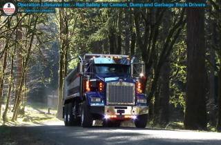 a dump truck drives down a tree-lined road